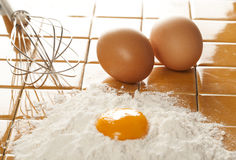 Eggs, flour and whisk on tile Royalty Free Stock Photo