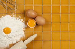 Eggs, flour and whisk on tile Royalty Free Stock Photos