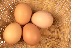 Eggs. Four brown eggs on a wicker basket Royalty Free Stock Images