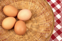 Eggs. Four brown eggs on a wicker basket stock image