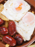 Eggs with french fries and small sausages. Royalty Free Stock Photo