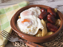 Eggs with french fries and small sausages Stock Photos