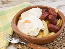 Eggs with french fries and small sausages. Stock Photos