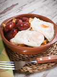 Eggs with french fries and small sausages Stock Image