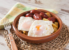 Eggs with french fries and small sausages. Royalty Free Stock Image
