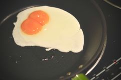 Eggs in fry pan, each egg with double yolks, double egg yolks fried in pan, close up of fried egg stock image