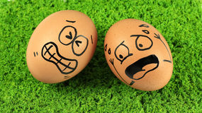 Eggs with funny faces, funny action  on green grass back Stock Photo