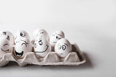 Eggs with funny faces in the package on a white background. Easter Concept Photo. Eggs. Faces on the eggs Stock Photography