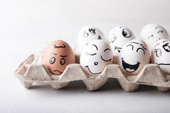 Eggs with funny faces in the package on a white background. Easter Concept Photo. Eggs. Faces on the eggs Stock Image