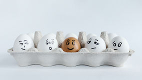 Eggs with funny faces in the package on a white background. Easter Concept Photo. Faces on the eggs stock photo