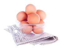 Eggs in the glass bowl, steel whisk and napkin Stock Image