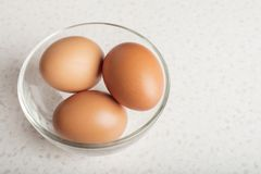Eggs in a glass bowl on a white table. Kitchen. Copy space Royalty Free Stock Image