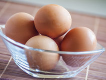 Eggs in glass bowl. On wooden table Stock Image