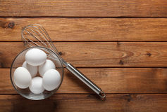 Eggs in a glass dish and wire whisk Royalty Free Stock Images