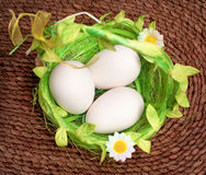 Eggs in green basket on wicker background Royalty Free Stock Images