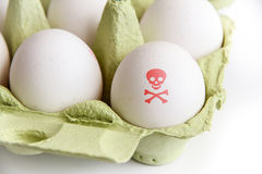Contaminated food: eggs in a green paper package with one of the eggs painted with a red poisonous risk symbol. Eggs in a green paper package with one of the royalty free stock photography