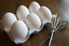 Eggs. Half dozen eggs resting in a ceramic egg holder on a kitchen wood cutting board with eggs whisks stock photo