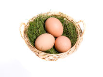 Eggs on a hay in the basket isolated on white. Three eggs on the grass in the wicker basket isolated on white close-up Royalty Free Stock Photos
