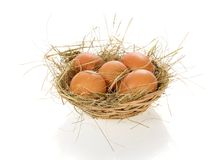Eggs, hay in a bast basket. Isolated on white Stock Photo