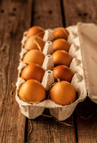 Eggs with hay in a carton box on rustic wood. Natural gold eggs with hay in a carton box on an old vintage planked wood table. Easter - rural or rustic kitchen Stock Images