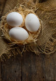 Eggs at hay nest in chicken farm Royalty Free Stock Photography