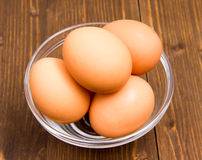 Eggs inside bowl on wood Royalty Free Stock Photos