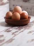 Eggs inside a clay plate over wooden background with copy space Royalty Free Stock Image