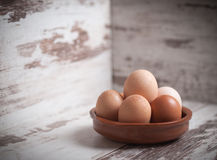 Eggs inside a clay plate over wooden background with copy space. In a studio shot Royalty Free Stock Photo