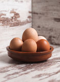 Eggs inside a clay plate over wooden background Royalty Free Stock Photo
