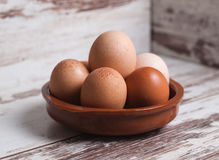 Eggs inside a clay plate over wooden background Royalty Free Stock Photography