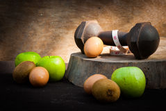 Eggs , kiwi , measuring type , apple and dumbbells for training Stock Image