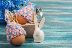 Eggs in knitted hats, flowers and decorative rabbit Stock Photography
