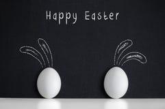 Eggs les rabbirs peints par witn sur le fond noir Photographie stock libre de droits