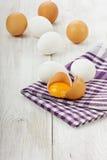 Eggs on a linen napkin. On a white wooden surface Stock Photos