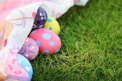 Eggs los colores en colores pastel, telas hermosas en hierba el día de Pascua Fotografía de archivo