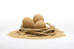 Eggs made of sand in the sandy nest. On white background. Creative picture can be used for Easter graphics Royalty Free Stock Images