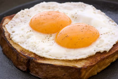 Eggs on Meat. Sunny side up on a slice of a meat loaf on a pan Stock Photo