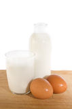 Eggs and milk in glass and bottle. Brown eggs and some milk in glass and bottle on white stock photos