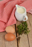 Eggs with milk and herbs on wooden table. Eggs with milk and herbs on wooden background royalty free stock photography