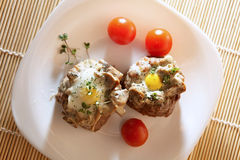 Eggs in the minced meat. Delicious quail eggs in the minced meat with mushrooms, decorated with cherry tomatoes and broccoli sprouts on white plates Stock Photos