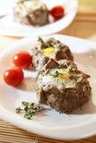 Eggs in the minced meat. Delicious quail eggs in the minced meat with mushrooms, decorated with cherry tomatoes and broccoli sprouts on white plates Stock Image
