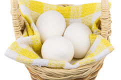 Eggs on napkin in wooden wicker basket Royalty Free Stock Image