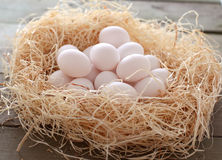 Eggs in a nest. Chicken eggs in a nest on the wooden background Stock Photo