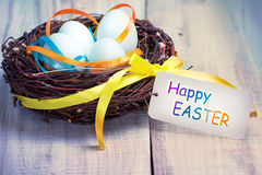 Eggs in nest happy Easter tag on wooden table. Royalty Free Stock Image