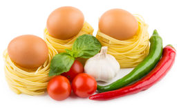 Eggs in nest from pasta, tomatoes, garlic and chili peppers Royalty Free Stock Image