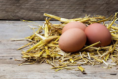 Eggs in a nest of straw on old wood, copyspace Royalty Free Stock Photos
