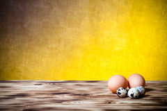 Eggs on new wooden board and burlap background. Selective focus. Stock Image