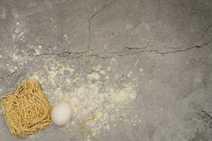 Eggs and noodles with the flour on a gray background stock photo