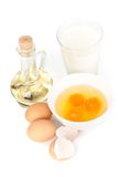 Eggs, oil, cup of milk and whisk Royalty Free Stock Images