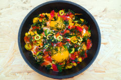 Eggs, olives, peppers, pan on table. Eggs and olives, peppers and corn, pan food on table Stock Image